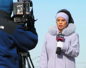 Aufsager einer Reporterin (sie berichtet für CN8 über eine Gas-Explosion, Foto: WikiCommons). Vor-Ort-Berichterstattung läuft Gefahr, immer seltener zu werden. Statt RedakteurInnen auf Reisen zu schicken oder auf lokale ReporterInnen zurückzugreifen wird auf Agenturmaterial zurückgegriffen.